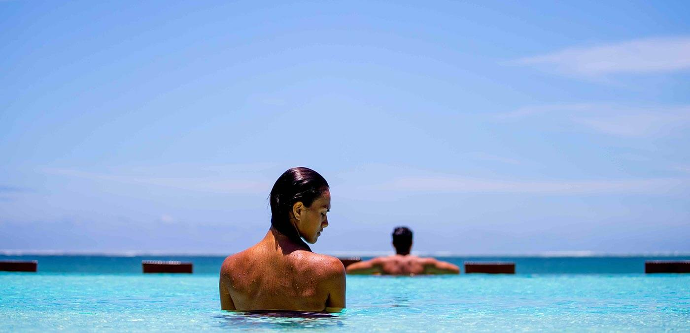 Couple enjoying the adults infinity pool overlooking Natadola Bay, InterContinental Fiji Golf Resort and Spa