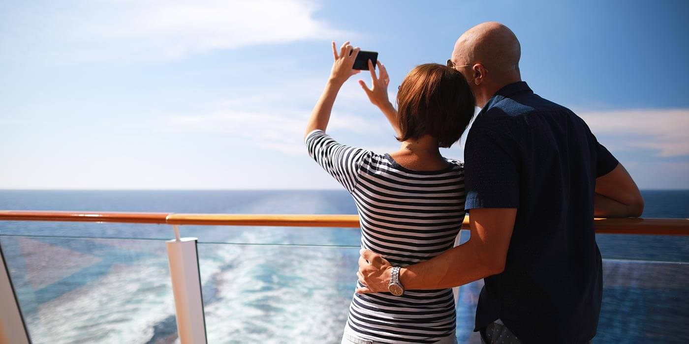 Couple traveling on cruise ship taking pictures