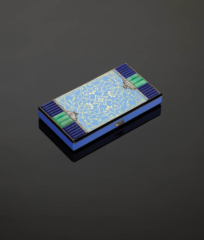 Vanity case with pale blue enamel decoration on the centre panel, fluted lapis lazuli and jade to the sides with baguette-cut diamond highlights. Van Cleef & Arpels, c. 1925.
