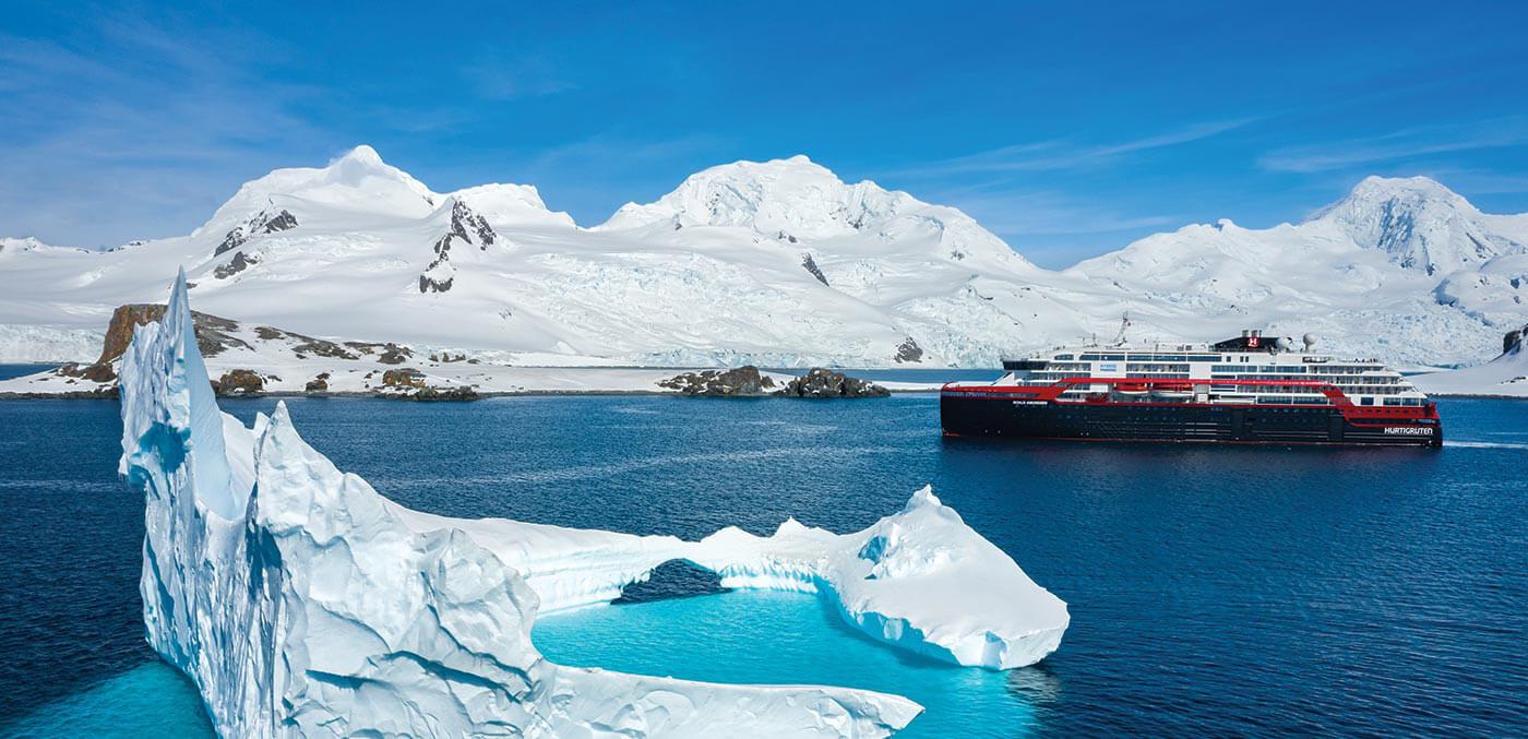 MS Roald Amundsen cruising past a crown-like iceberg