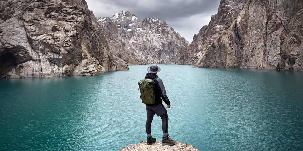 Man in hat with backpack at mountain lake Kel Suu near Chinese border in Kyrgyzstan