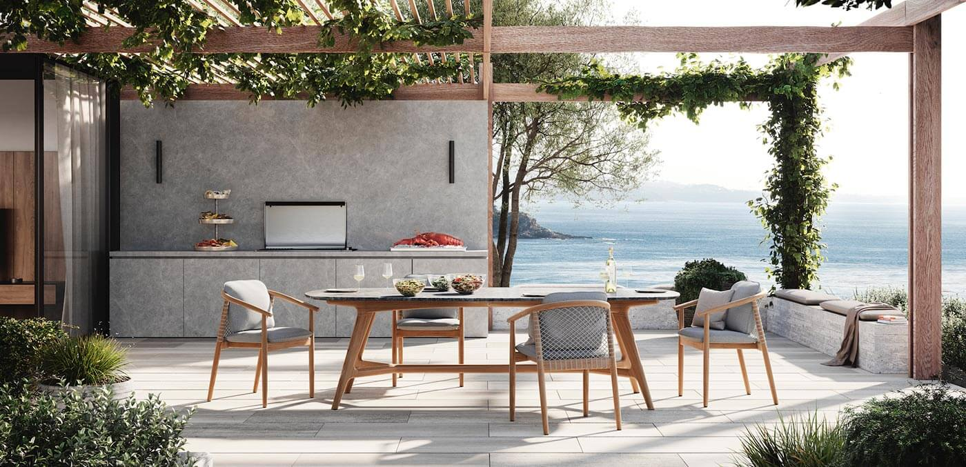 Cosh Living's 'Forrest' Elyptical Stone Table paired with 'Forrest' Armchairs, cutting a striking outdoor form