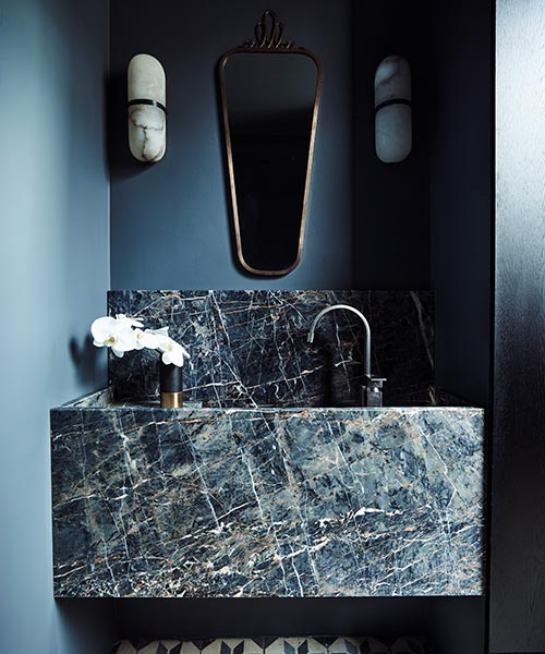 Bijoux powder room features a dramatic stone basin