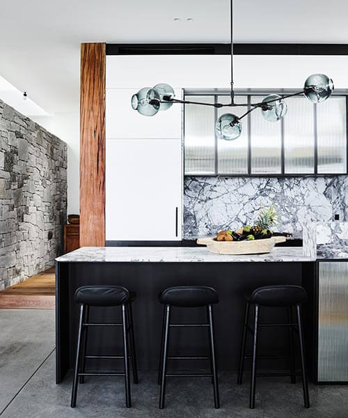 Designer lighting and dramatic countertops in the kitchen